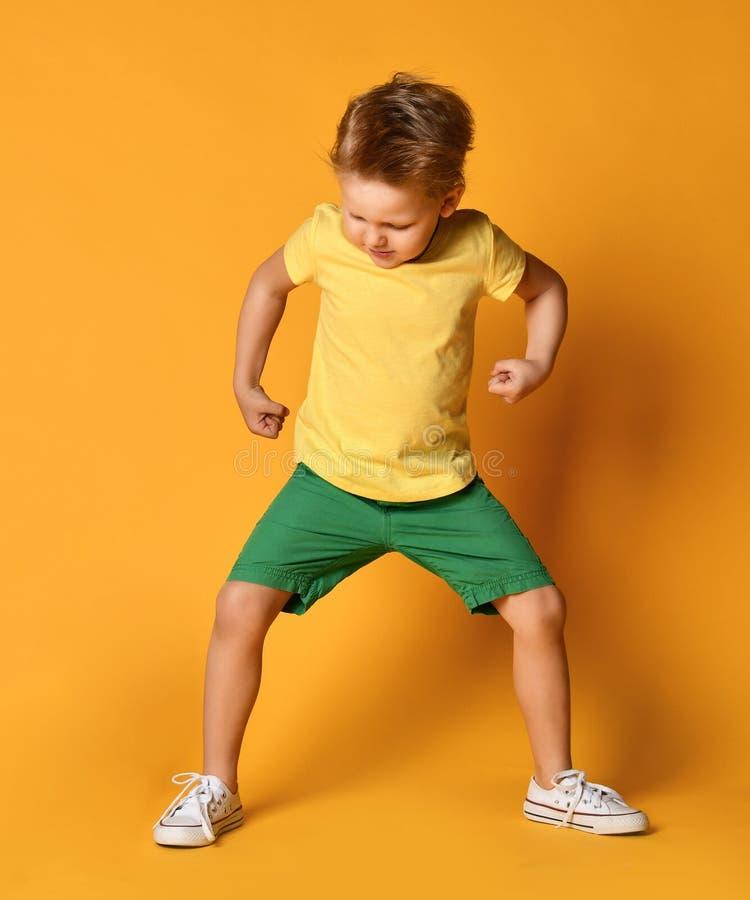 Jungenkind im gelben T-Shirt und in den grünen kurzen Hosen, die Haltungen wie ein Riese fungieren, stampft demonstriert laut Ene stockfotografie