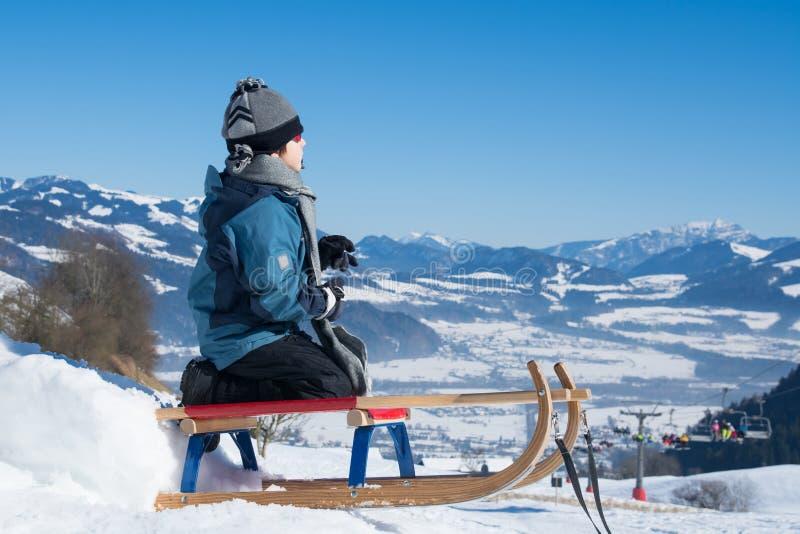 Jungenkind im Winter auf Schlitten lizenzfreie stockbilder