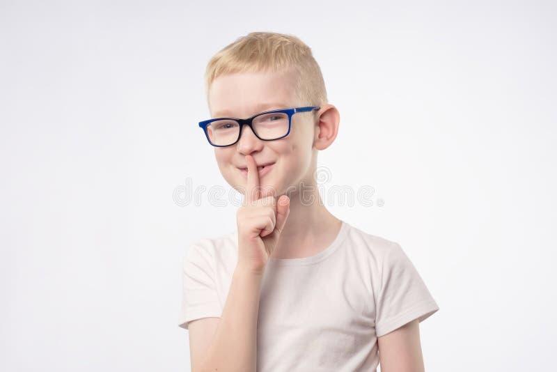 Jungenkind zeigt das Zeichenhandzeichen, das Finger auf Lippen hält stockfoto