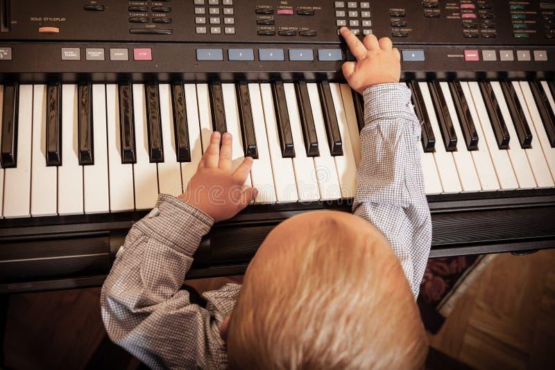 Jungenkinderkind, das auf digitalem Tastaturklaviersynthesizer spielt stockfotografie