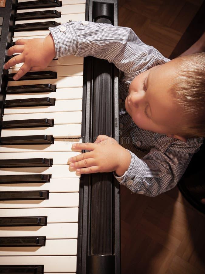 Jungenkinderkind, das auf digitalem Tastaturklaviersynthesizer spielt lizenzfreie stockfotografie