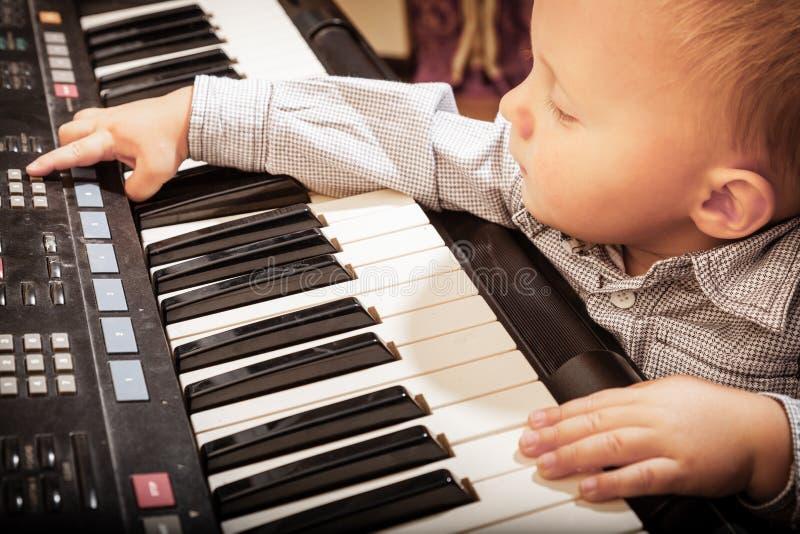 Jungenkinderkind, das auf digitalem Tastaturklaviersynthesizer spielt lizenzfreie stockfotos