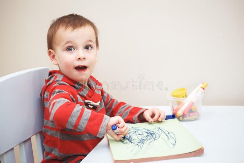 Jungenkleinkindzeichnung mit Farbe zeichnet Markierungen auf Papier im Album an lizenzfreie stockfotos