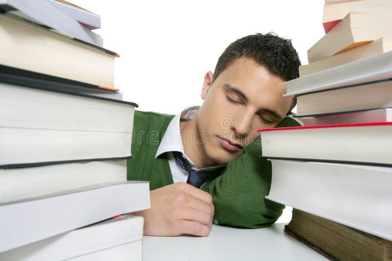 Jungenkursteilnehmer, der über Stapelbüchern über Schreibtisch schläft lizenzfreie stockfotografie