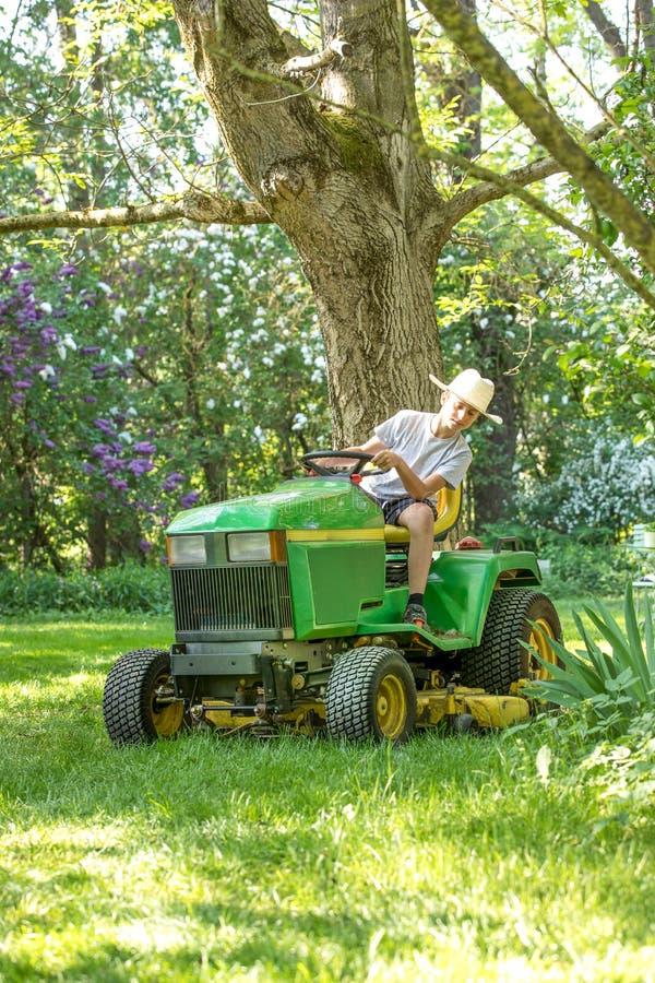 Jungenmann auf einem Traktor stockbild
