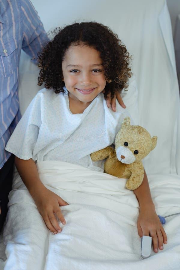 Jungenpatient, der auf Bett im Bezirk am Krankenhaus sitzt lizenzfreie stockbilder