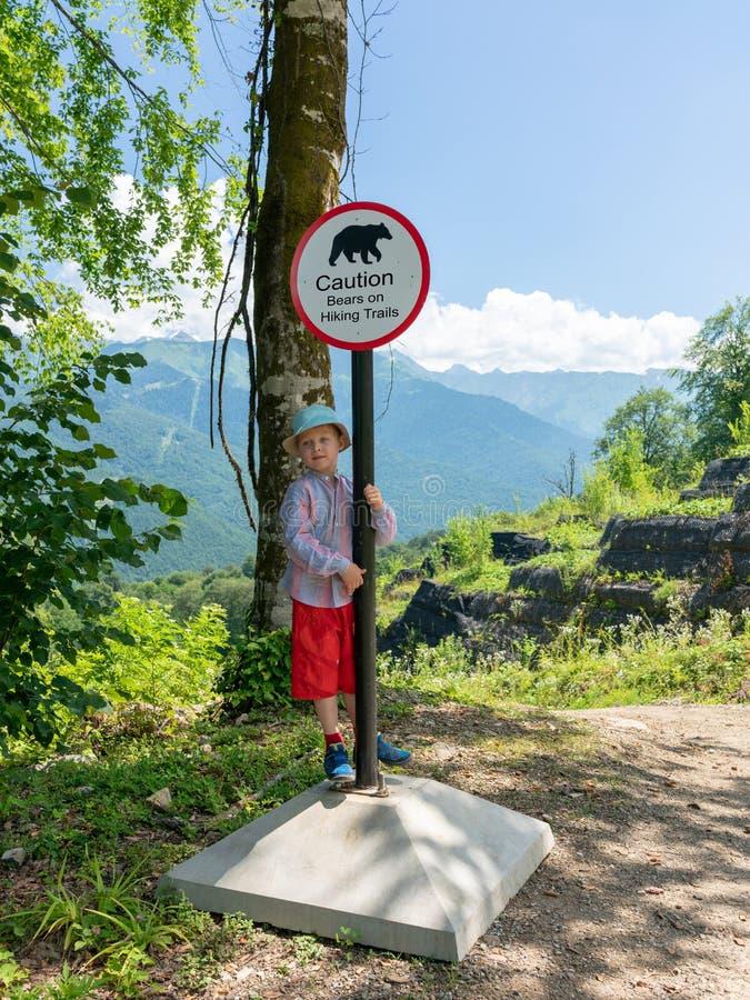 Jungenreisender steht nahe dem Zeichen von Vorsichtbären lizenzfreie stockbilder