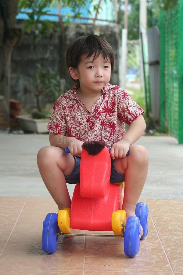 Jungenreiten auf Spielzeugpferd lizenzfreie stockbilder