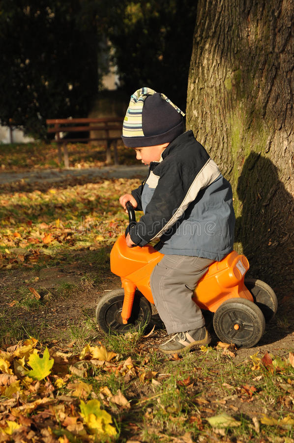 Jungenreitspielzeugmotorrad stockfotografie