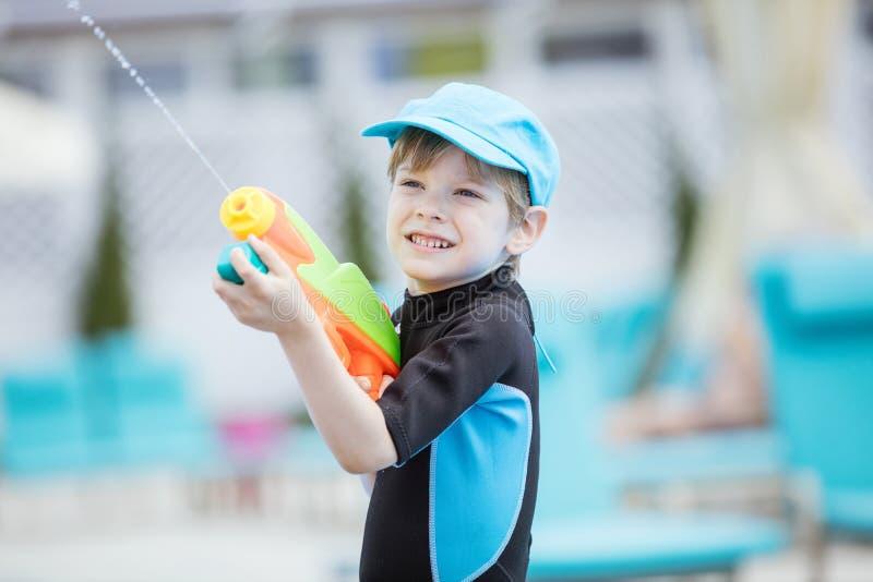 Jungenschießenwasserwerfer draußen lizenzfreie stockfotografie