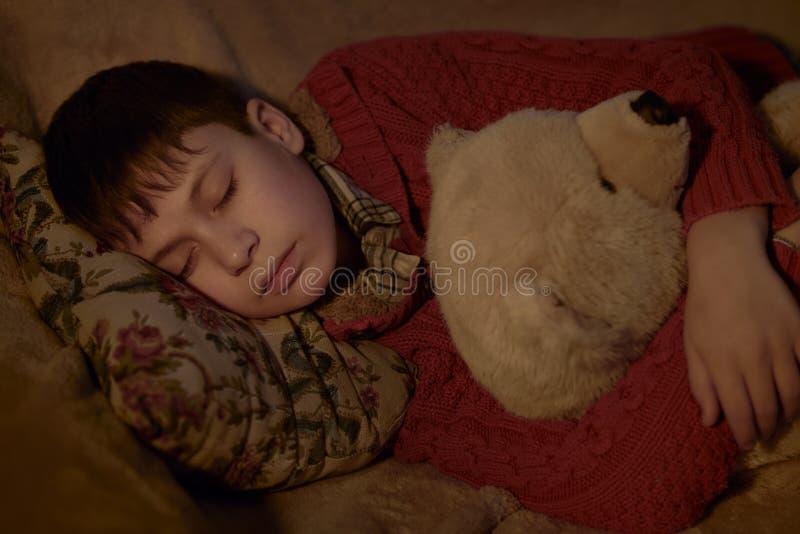 Jungenschlaf im Bett mit Bärnspielzeug lizenzfreies stockbild