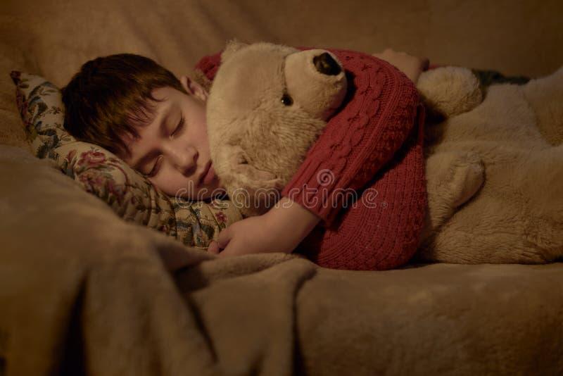 Jungenschlaf im Bett mit Bärnspielzeug stockfotografie