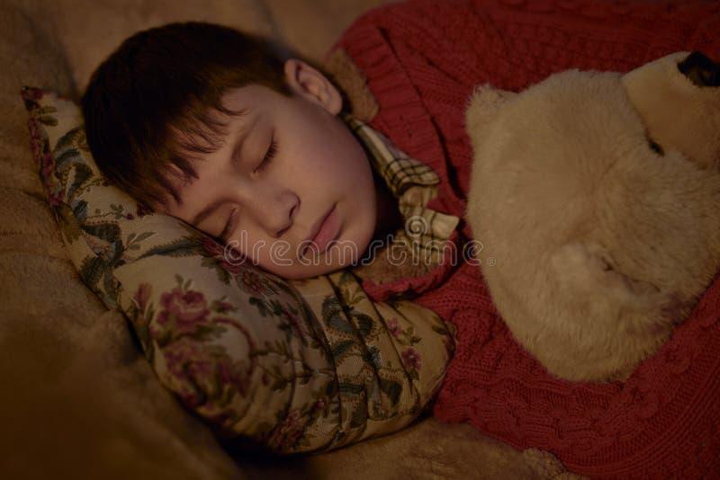 Jungenschlaf im Bett mit Bärnspielzeug lizenzfreies stockfoto