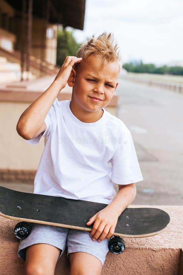Jungenschlittschuhläufer, der mit Skateboard aufwirft stockfotos