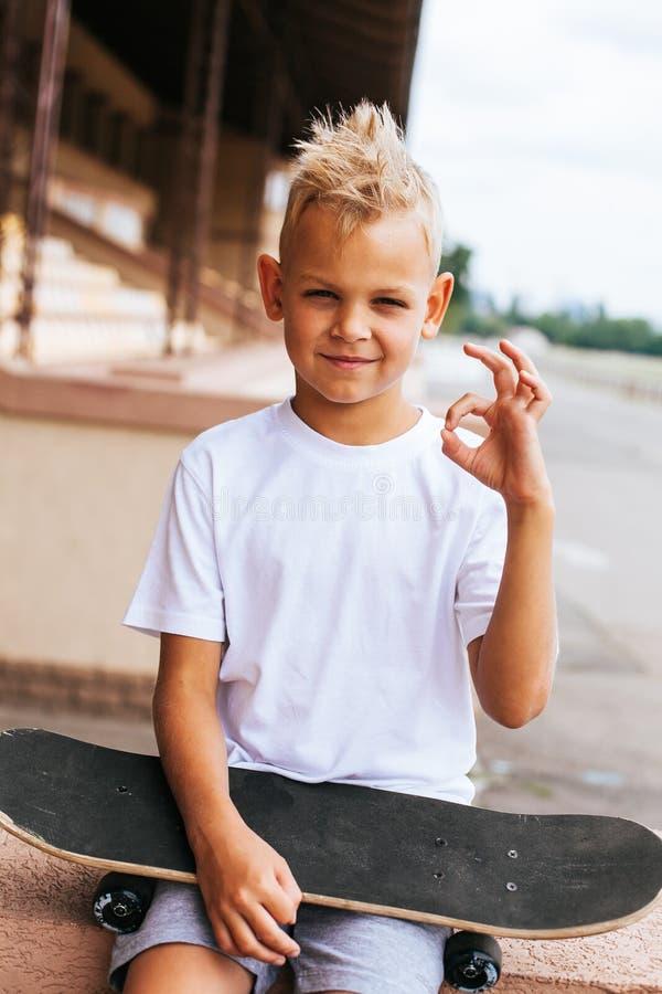 Jungenschlittschuhläufer, der mit Skateboard aufwirft stockbild