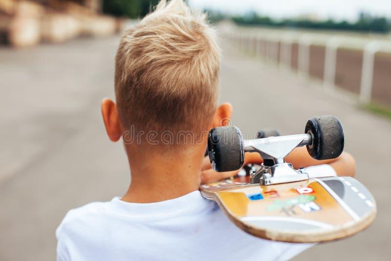 Jungenschlittschuhläufer, der mit Skateboard aufwirft stockfoto