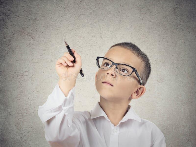 Jungenschreiben mit einem Stift auf Tafel stockfotos