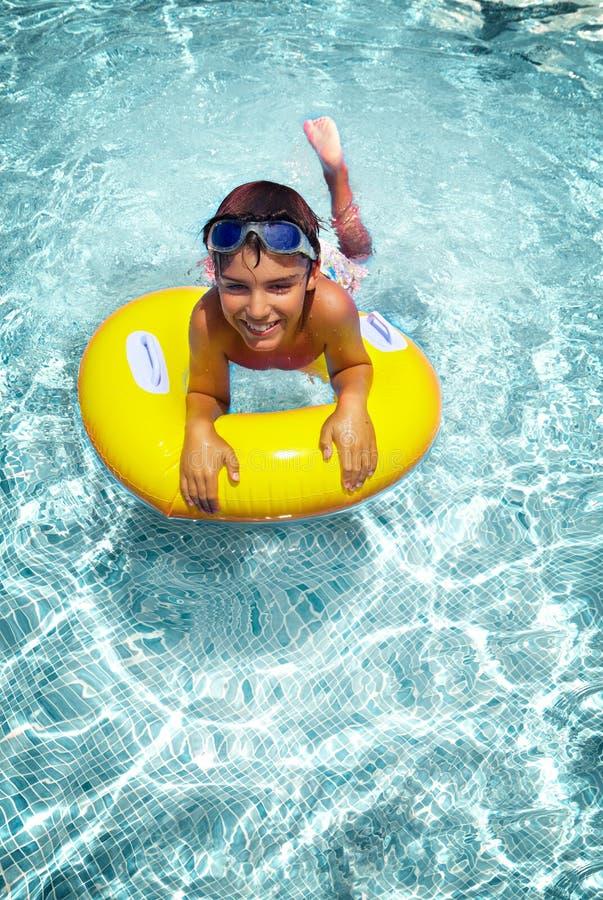 Jungenschwimmen auf Gummiring im Pool lizenzfreie stockbilder
