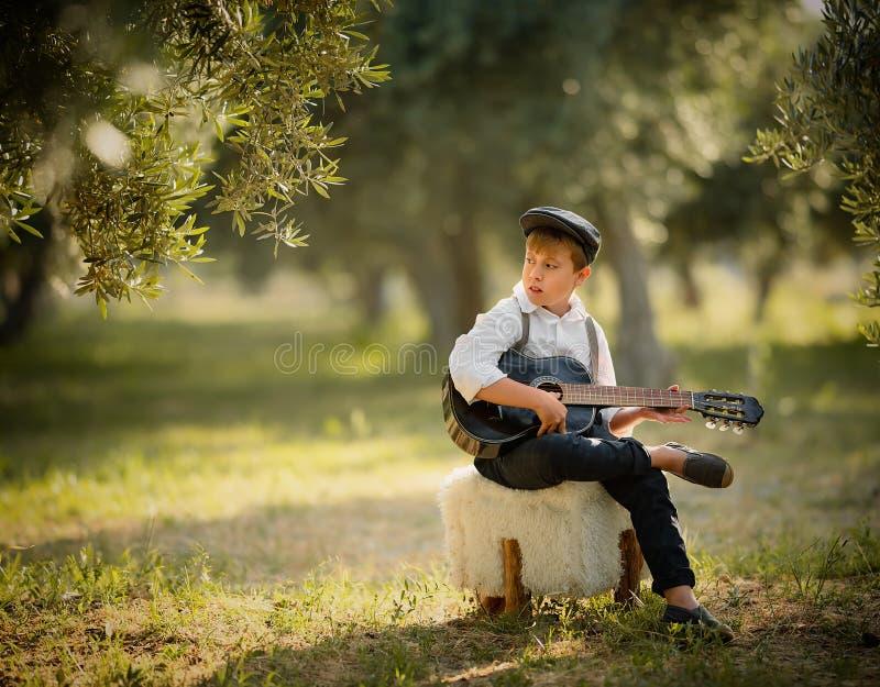 Jungenspiel auf Gitarre zu Hause am sonnigen Tag lizenzfreies stockbild