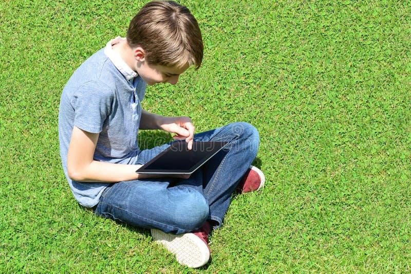 Jungenspiel auf seinem neuen Tabletten-PC stockbilder