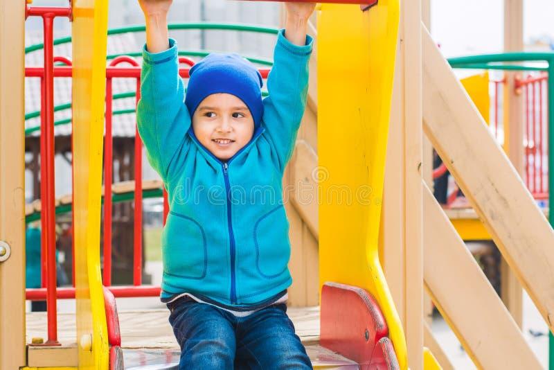 Jungenspiele auf dem Spielplatz lizenzfreies stockbild