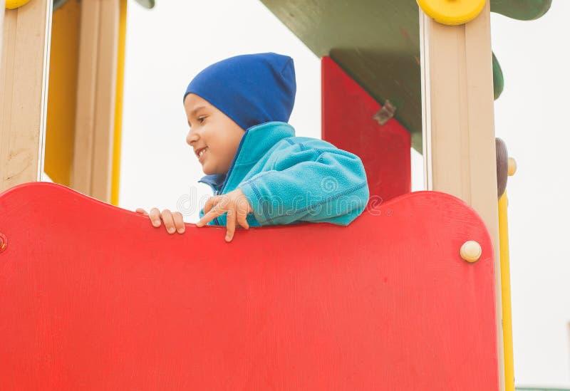 Jungenspiele auf dem Spielplatz lizenzfreie stockbilder