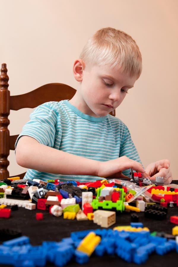 Jungenspiele mit lego lizenzfreie stockbilder