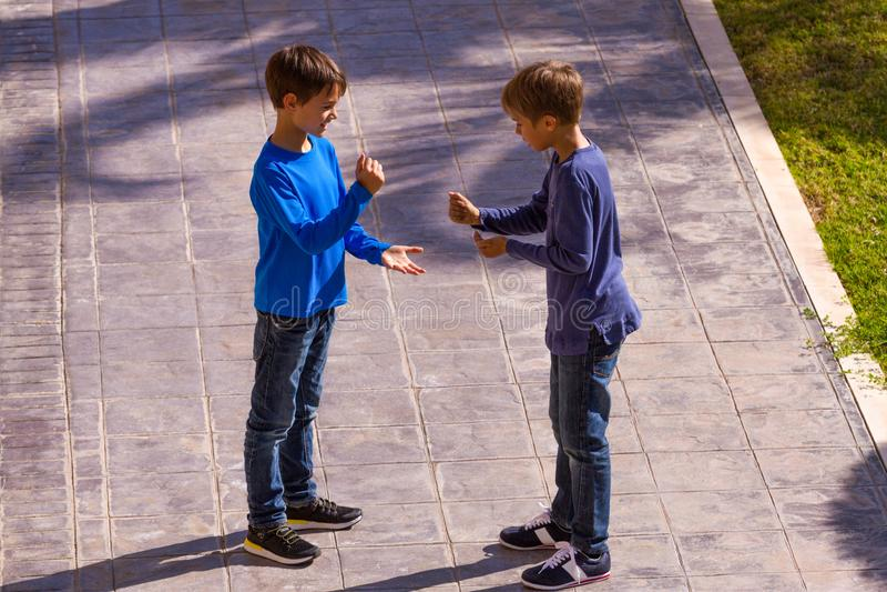 Jungenspielspiel-Rockpapier scissor am sonnigen Tag im Yard lizenzfreie stockfotos