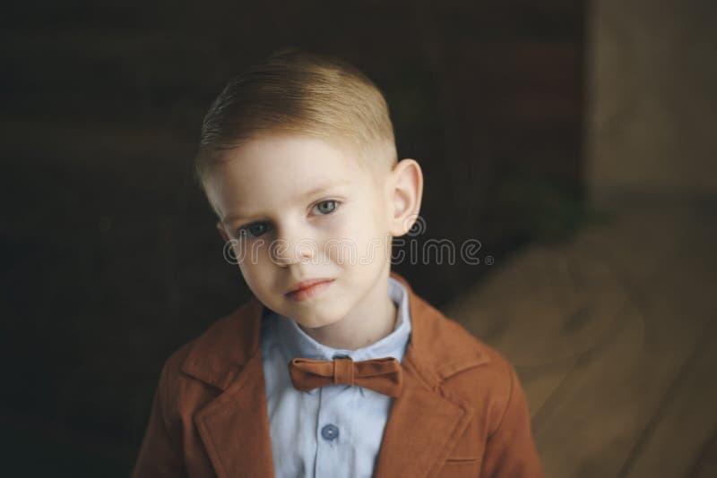 Jungenvorschüler mit braunen Augen im karierten Hemd und in der roten Fliege, Blicke weg, moderne Frisur, stockbilder