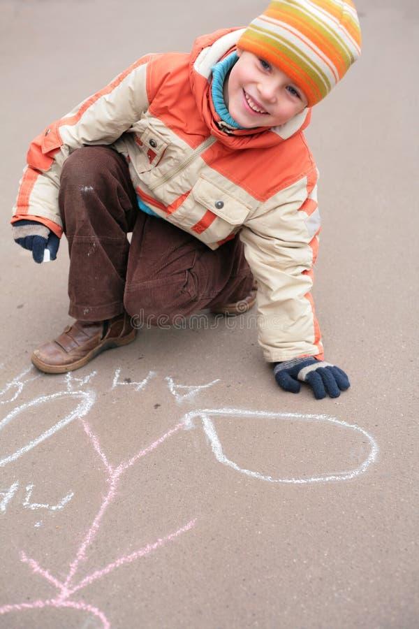 Jungenzeichnung durch Kreide auf Asphalt lizenzfreie stockfotos