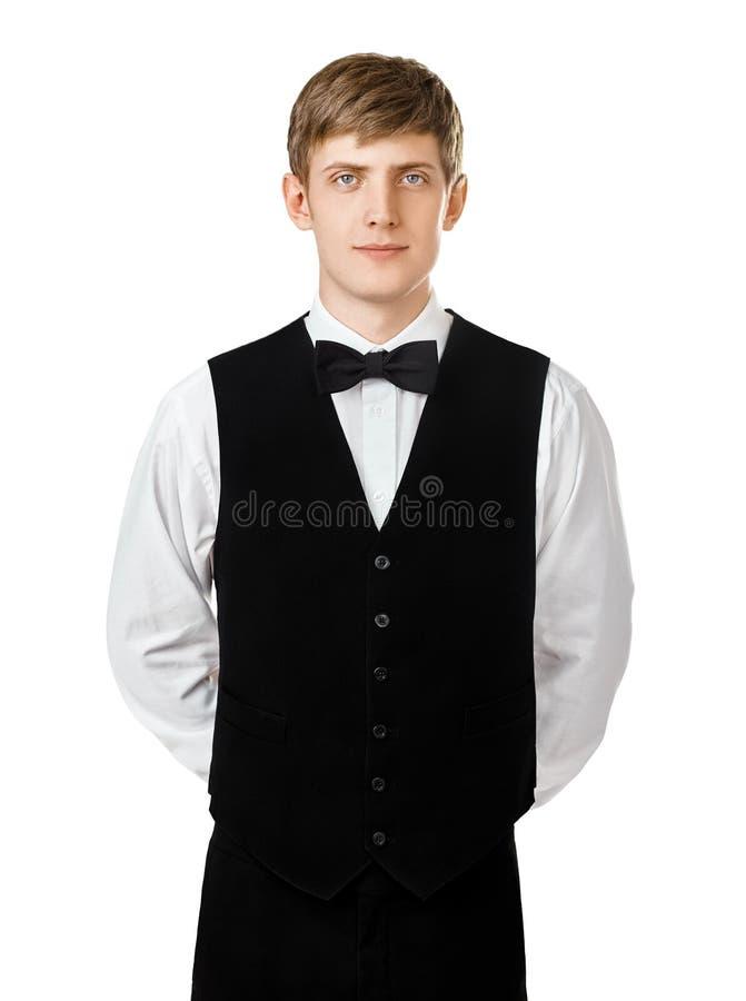 Junger überzeugter Kellner, der mit den Händen hinter seinem zurück steht lizenzfreie stockbilder