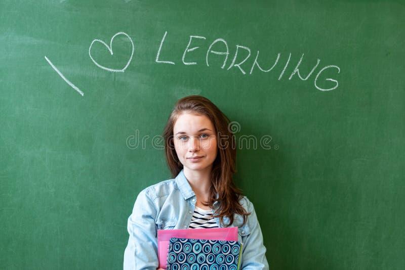 Junger überzeugter lächelnder weiblicher hoher Schüler, der vor Tafel im Klassenzimmer, Lehrbücher halten steht stockfotografie