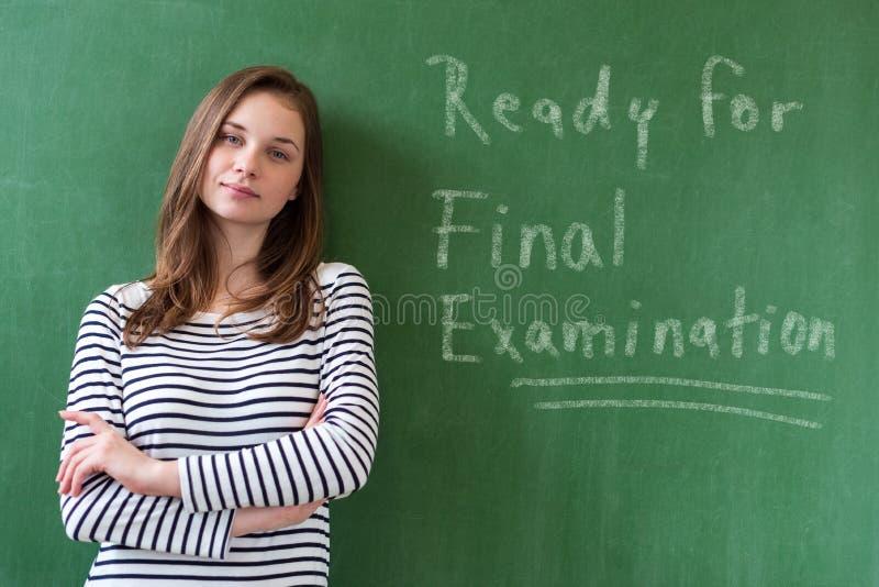 Junger überzeugter lächelnder weiblicher hoher Schüler, der vor Tafel im Klassenzimmer steht, wenn ihre Arme gekreuzt sind lizenzfreie stockfotografie