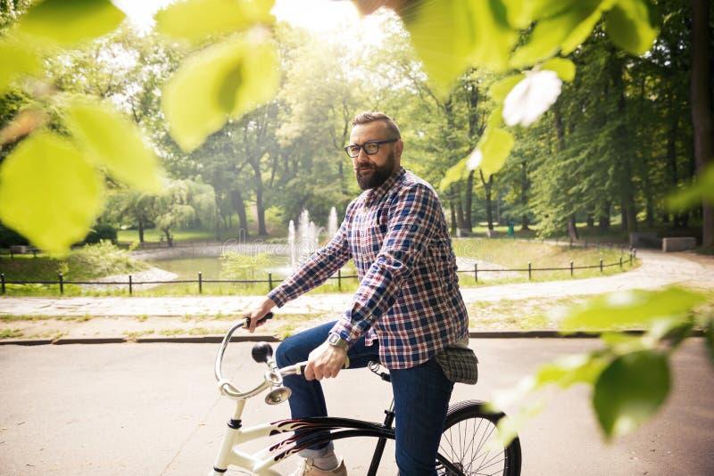Junger überzeugter Mann, der auf Fahrrad am Park sitzt stockfotos