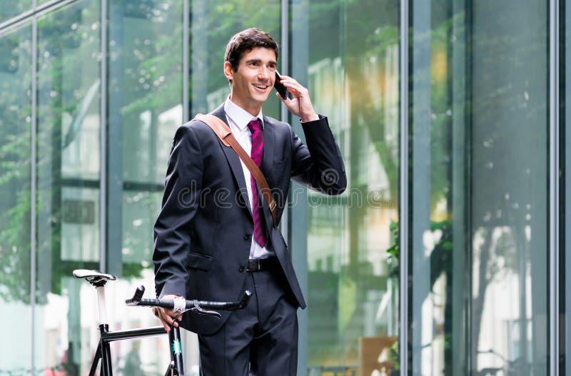 Junger überzeugter Mann, der am Handy nach Fahrrad commutin spricht lizenzfreies stockbild