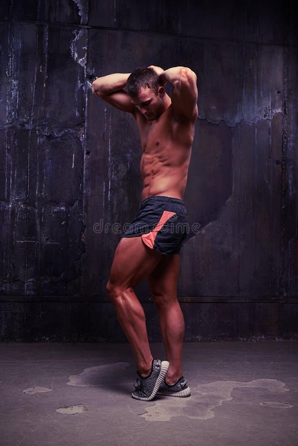 Junger überzeugter muskulöser Mann, der die Entlastung seines Unterleibs zeigt lizenzfreies stockbild