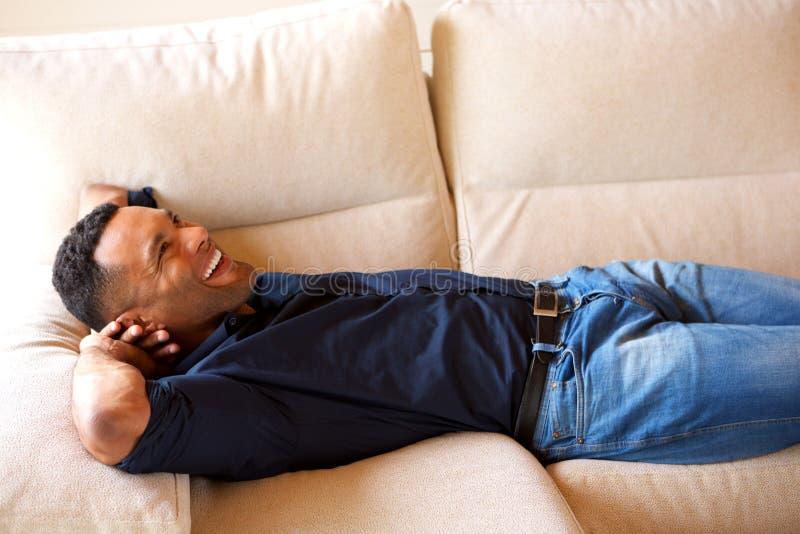 Junger afrikanischer Kerl, der auf Couch stillsteht und zu Hause lächelt lizenzfreie stockfotografie