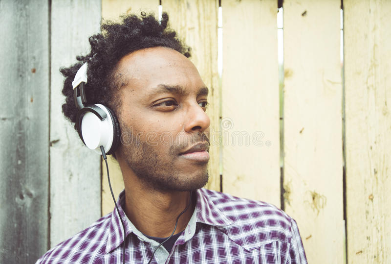 Junger afrikanischer Mann, der Musik hört stockbild