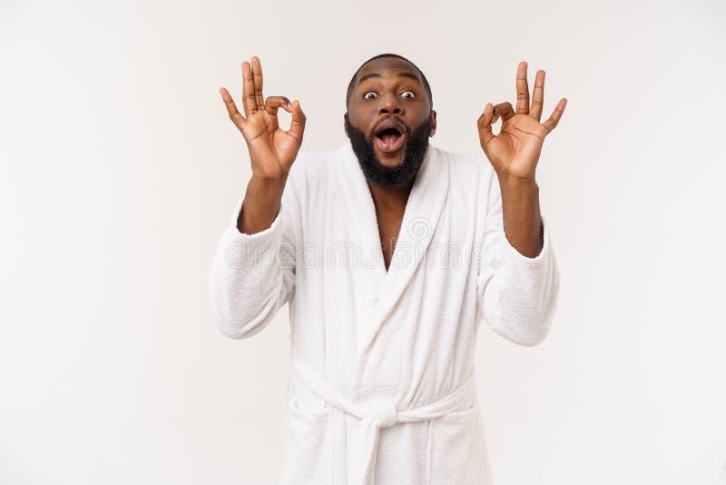 Junger afrikanischer Mann im Bademantel für die Hautpflege sich vorbereiten, die okayfingerzeichen zeigt Menschliches Gef?hlkonze stockfoto