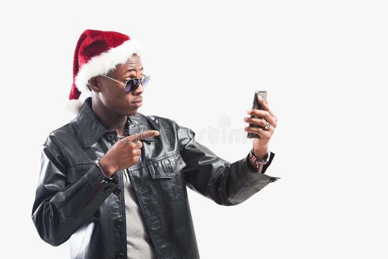 Junger afrikanischer Mann mit Handy zur Weihnachtszeit lizenzfreie stockbilder