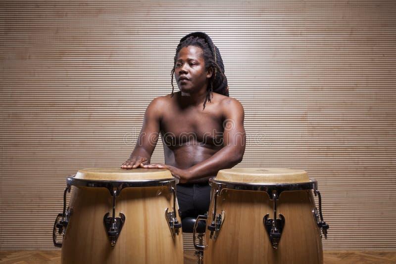 junger afrikanischer Mann spielt Congas stockfotos