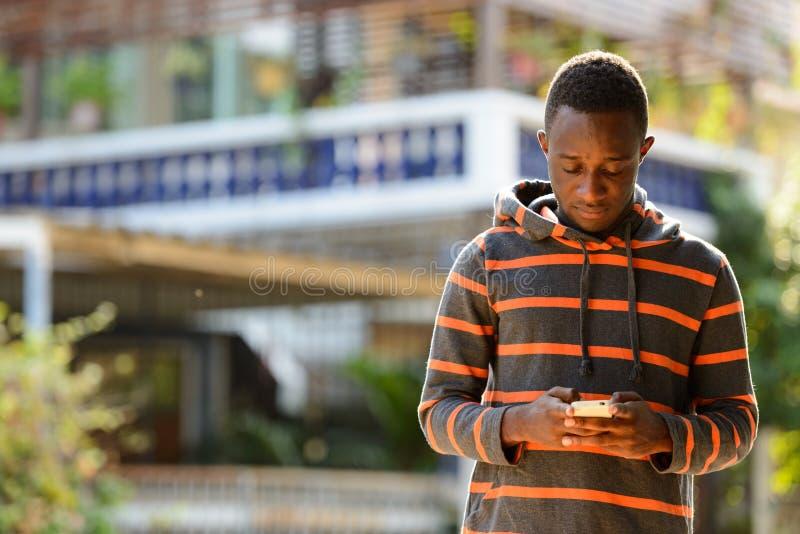 Junger afrikanischer Mann unter Verwendung des Handys draußen lizenzfreie stockbilder