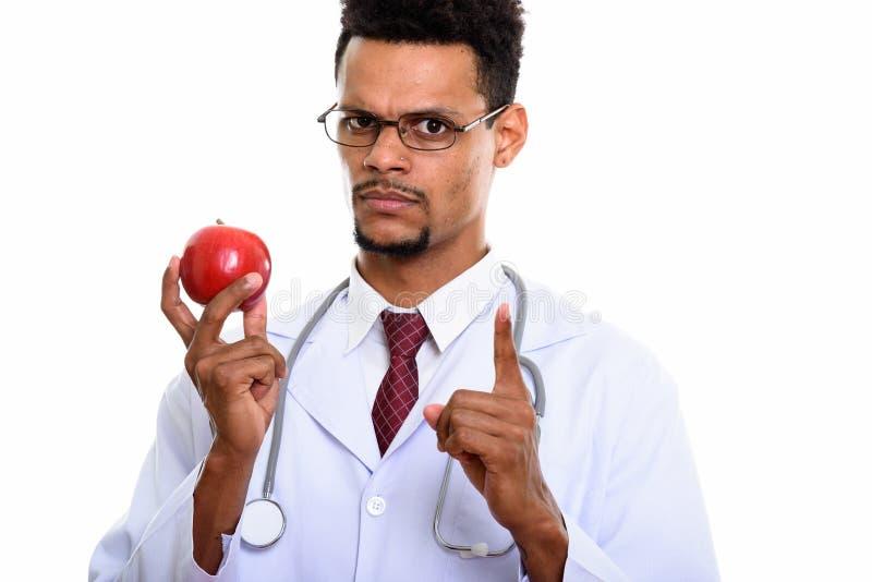 Junger afrikanischer Manndoktor, der roten Apfel beim Zeigen des Fingers hält stockfotos