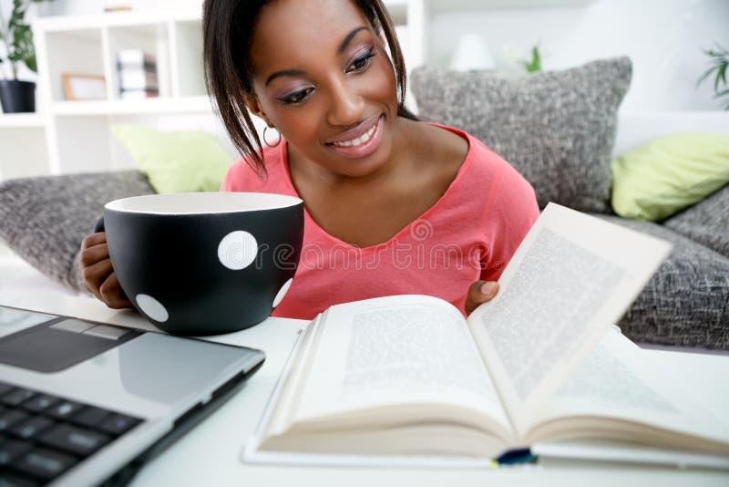 Junger afrikanischer Student, der zu Hause lernt stockbilder