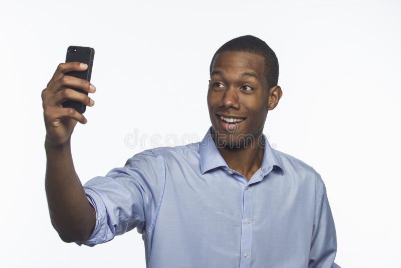 Junger Afroamerikaner, der ein selfie Foto mit dem Smartphone, horizontal macht lizenzfreie stockbilder