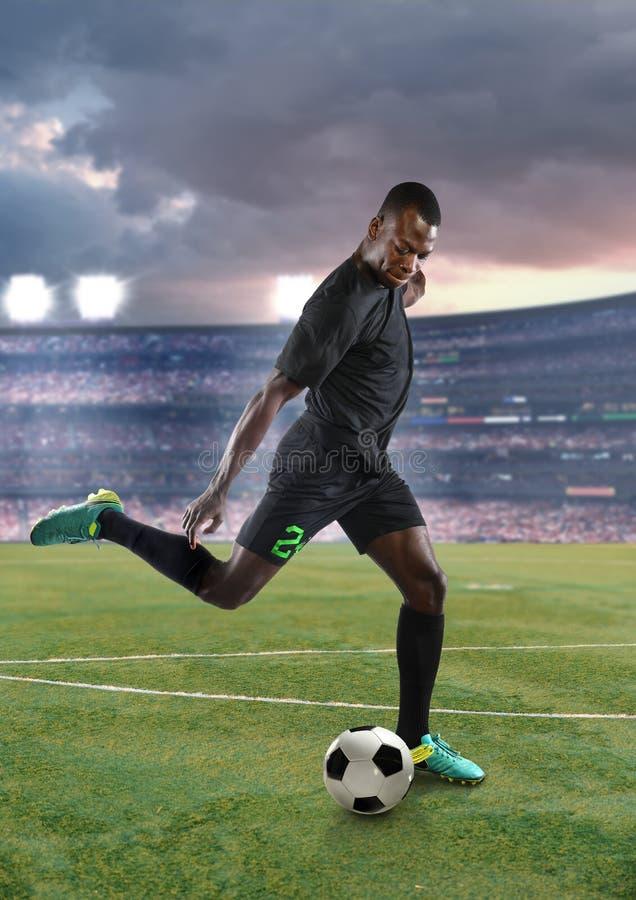 Junger Afroamerikaner-Fußball-Spieler-tretender Fußball lizenzfreies stockbild