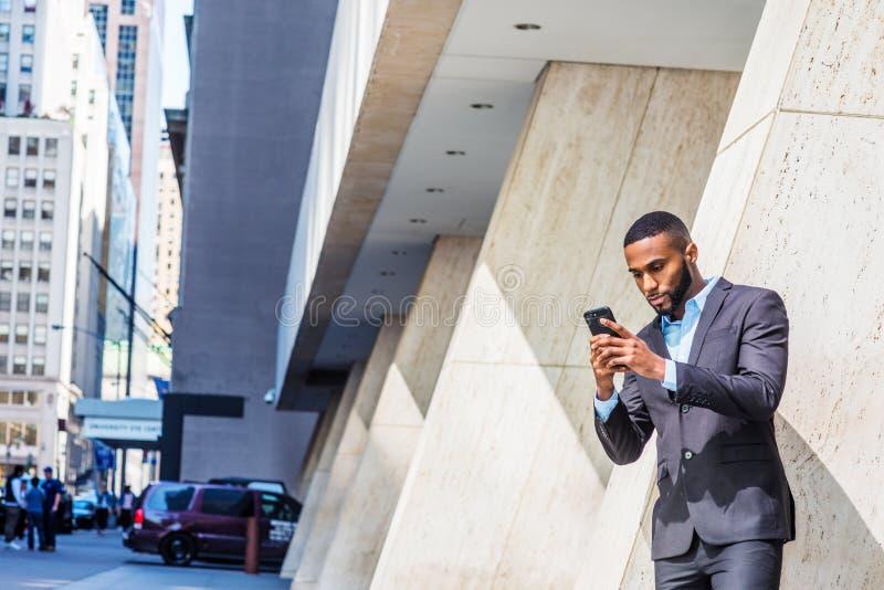 Junger Afroamerikaner-Geschäftsmann mit Bart, kurzes Haar, simsend am Handy draußen in New York City lizenzfreie stockbilder