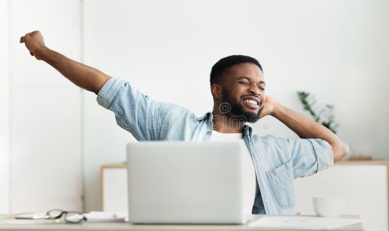 Junger Afroamerikanerfreiberufler, der Bruch hat und am Arbeitsplatz ausdehnt lizenzfreie stockbilder