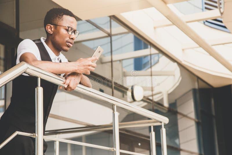 Junger AfroamerikanerGeschäftsmann in der Klage und Brillen, die am Telefon auf dem Hintergrund des Geschäftszentrums sprechen lizenzfreie stockfotografie