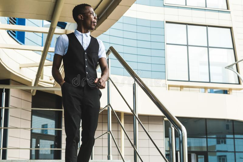 Junger AfroamerikanerGeschäftsmann in der Klage und Brillen, die am Telefon auf dem Hintergrund des Geschäftszentrums sprechen lizenzfreie stockbilder